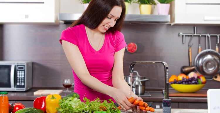 Photo of young woman washes the vegetables in domestic kitchen