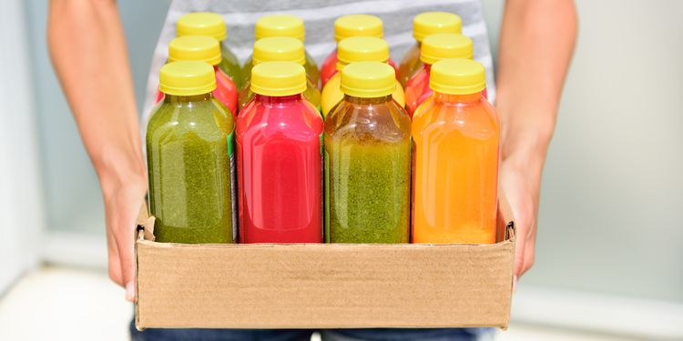 Photo of a person holding different colored bottles of cold pressed juice