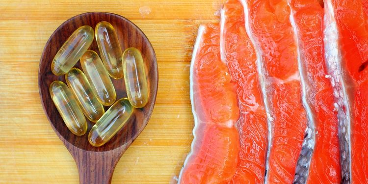 Photo of fish oil caps in a spoon next to fish filet