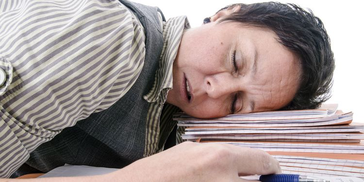 Photo of a student sleeping on a pile of books