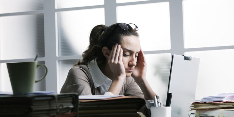 Photo of woman holding her head, having migraine in office