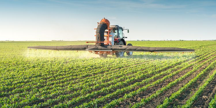 Photo of tractor in field applying the pesticides on crops