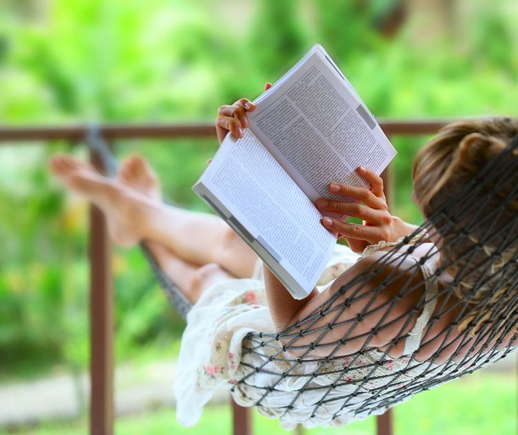 Photo of a girl Reading Book Lying In A Hammock