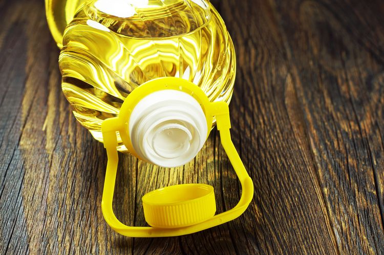 Photo of Canola Oil opened bottle lying on table