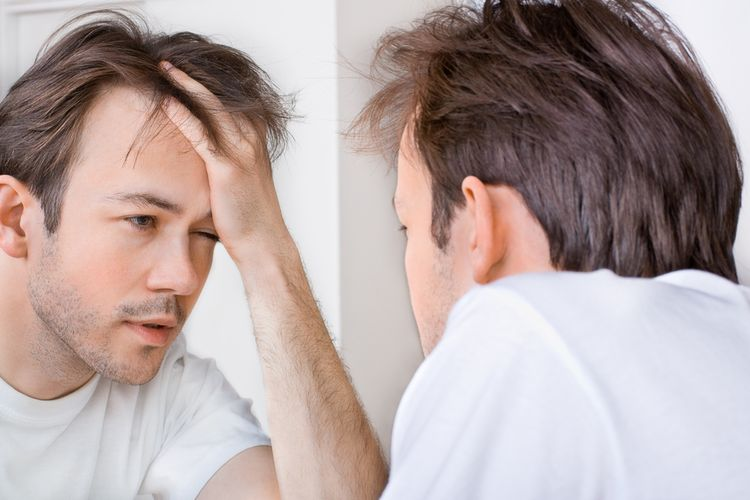 Photo of a man with hangover In The Morning looking at a mirror