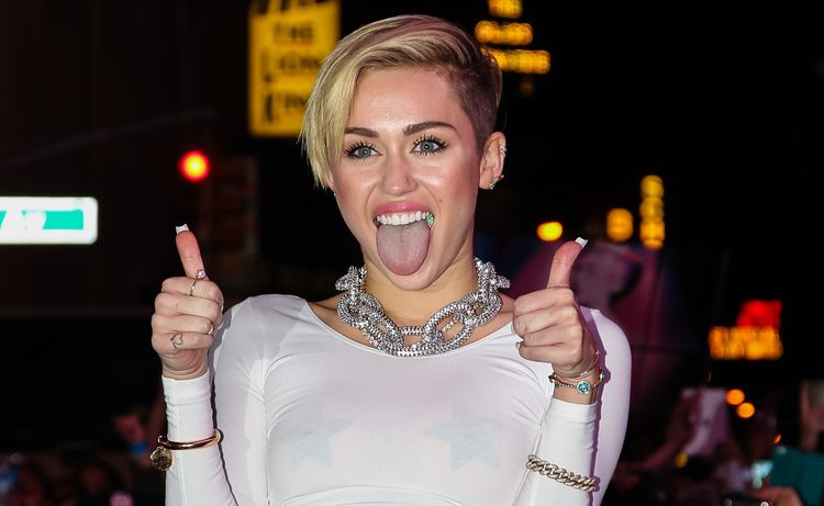 Photo of Miley Cyrus showing two thumbs up and tongue