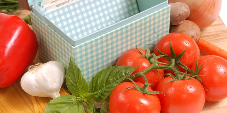 Photo of a box with recipes next to a fresh tomato