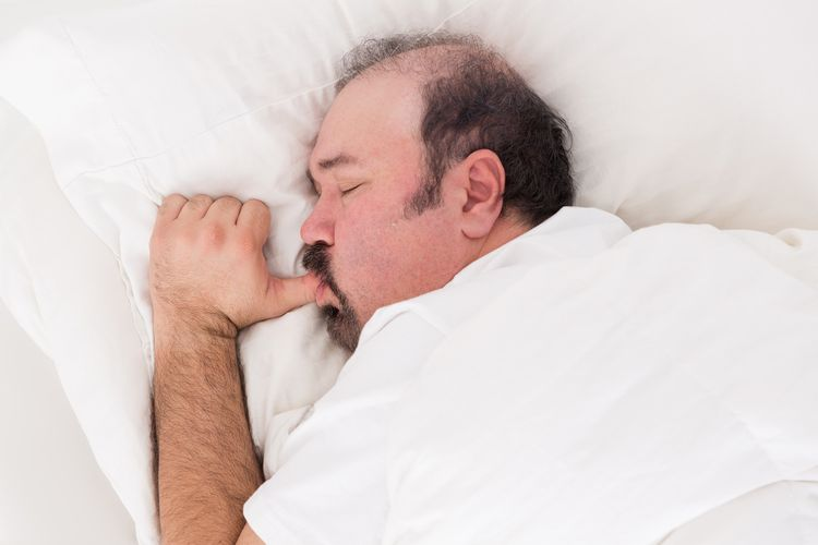 Photo of a adult man with sucking thumb and sleeping in bed
