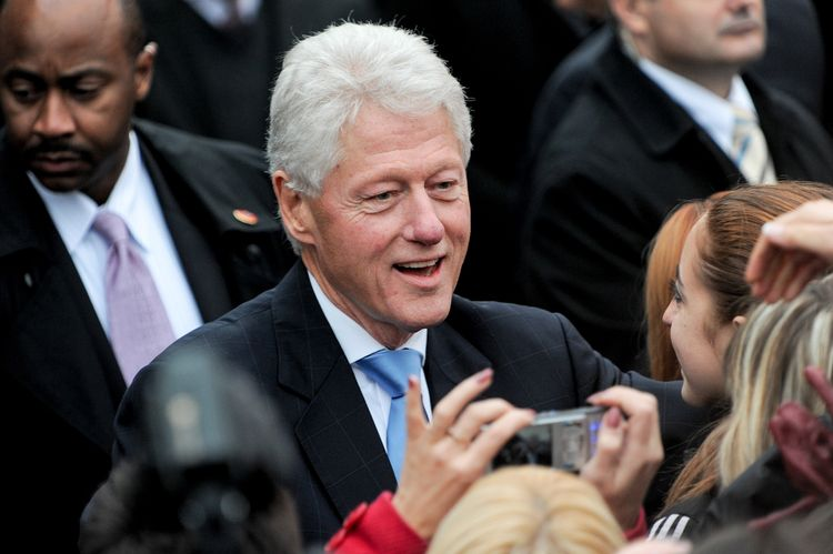 Photo of Bill Clinton smiling in a front of people