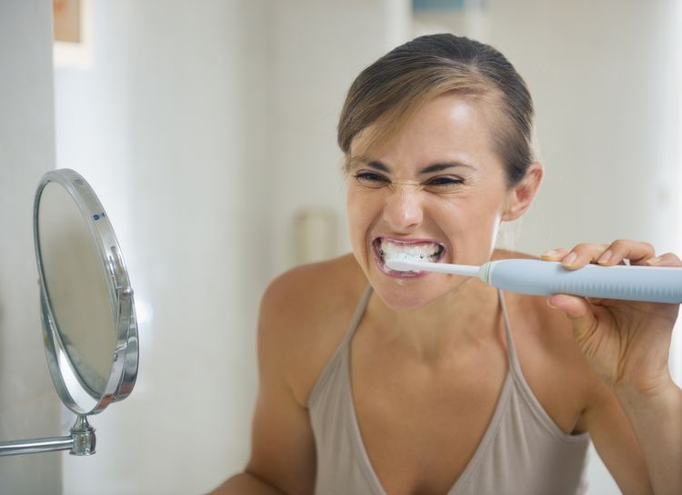 Photo of a woman Brushing Teeth with Coconut Oil