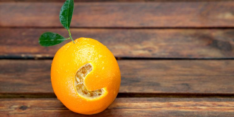 Photo of fresh orange with letter C cut into it