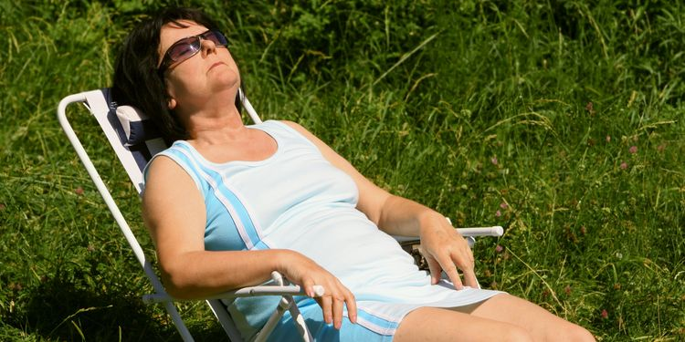 Photo of senior woman laying in beach chair relaxing