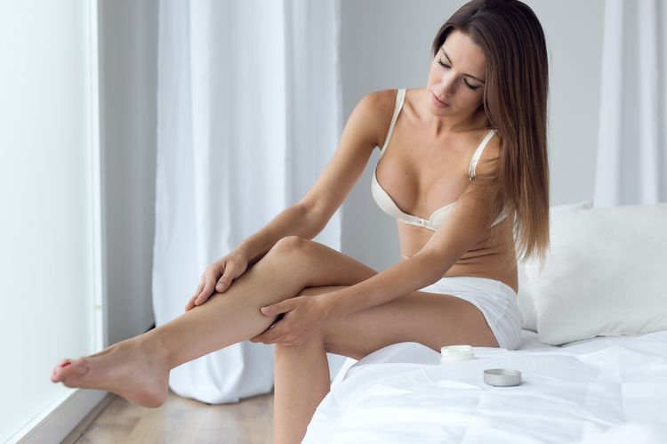 Photo of a Woman Applying Coconut Oila As Moisturizer On Legs
