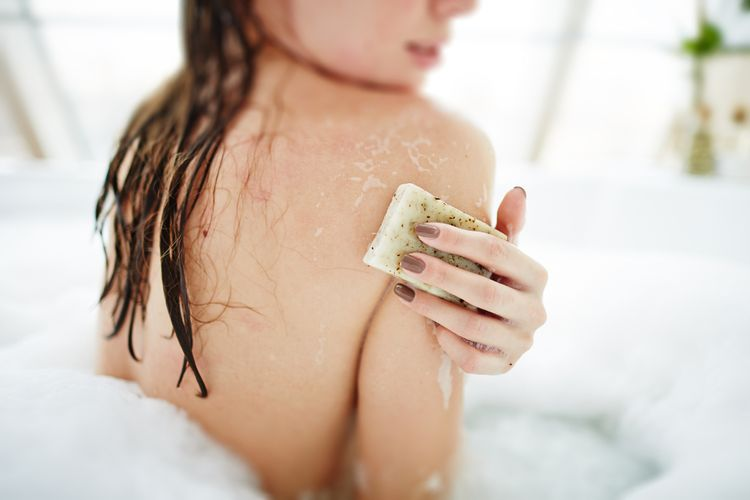 Photo of a Woman Exfoliating Her Skin With Soap