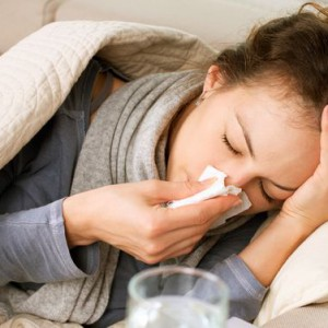 Woman lying in bed with runny nose having flu