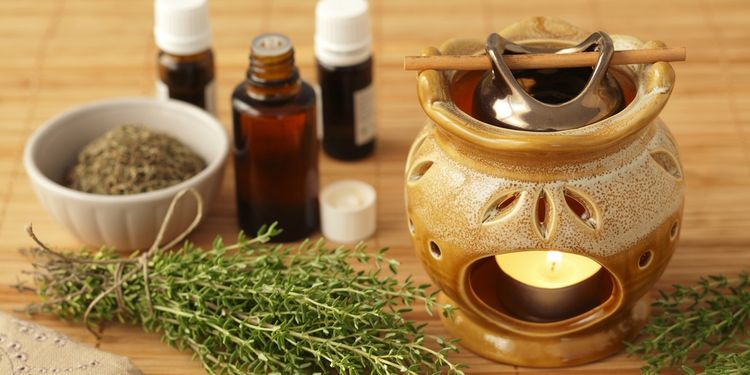 Photo of herbs, oils and diffuser with a candle on a table