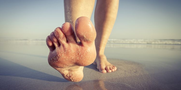 Close up of a woman walking on wet sand on the beach