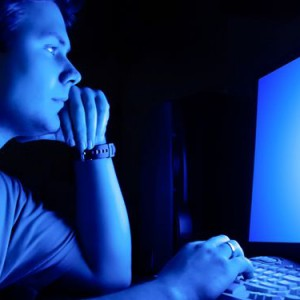 Man staring at the blue screen in dark room