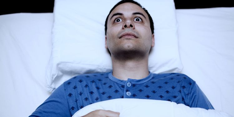 Insomniac man lying in bed with eyes wide open