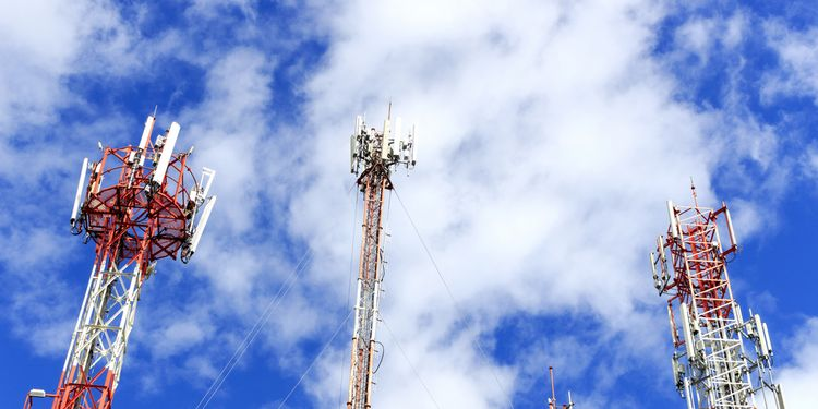 Photo of cell phone and communication towers against blue sky