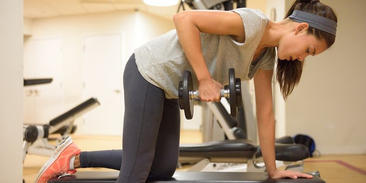 Woman doing dumbbell row on a bench in gym