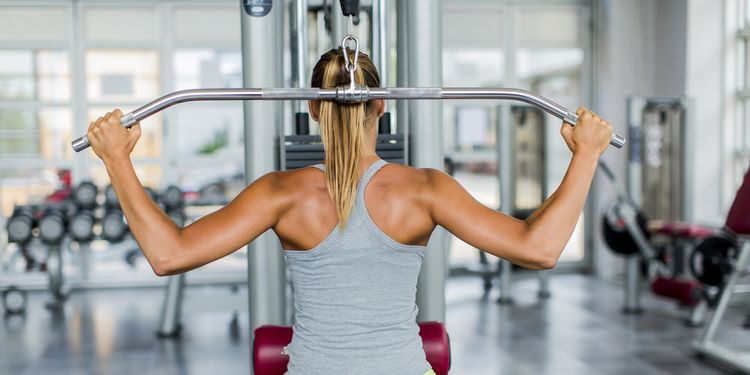 Pretty blonde girl doing lat pulldown at the gym