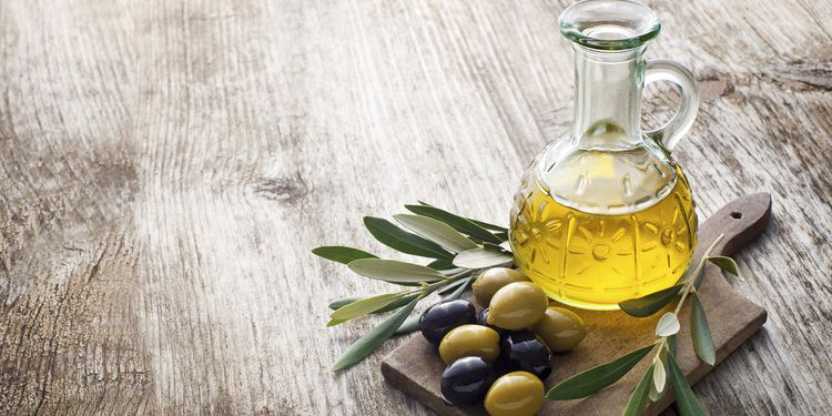 Olive oil with raw olives on table