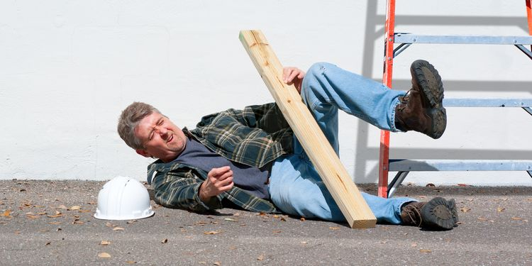 Photo of an injured construction worker who just fell from a ladder on a construction job