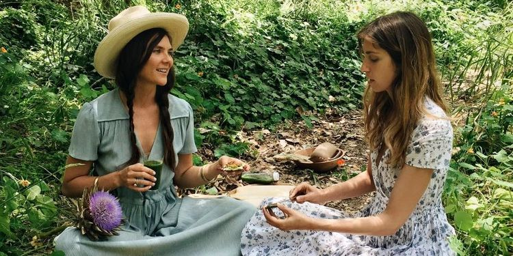 Wellness warrior Amanda Chantal Bacon and her friend eating snacks that tap into the natural healing power of raw vegetables, fruits, petals, herbs, roots, nuts, and seaweeds