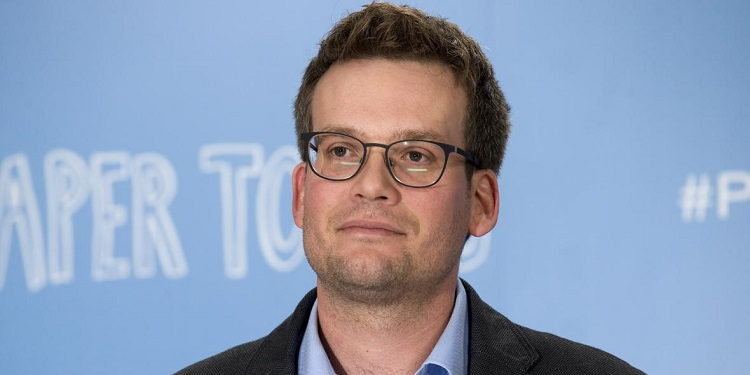 A photo of John Green with a blue background