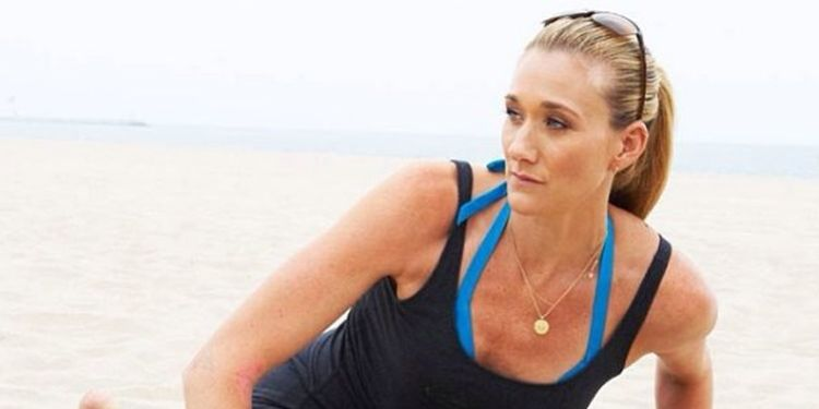 Wellness warrior Kerri Walsh Jennings is stretching on the beach.