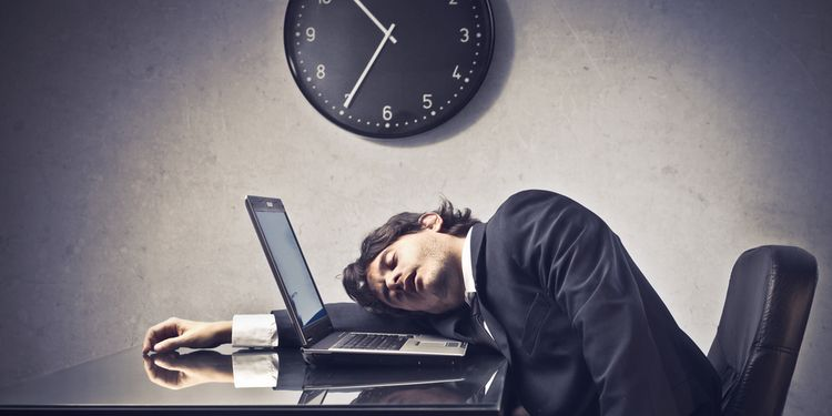 Photo of tired businessman sleeping on a laptop with clock in the background