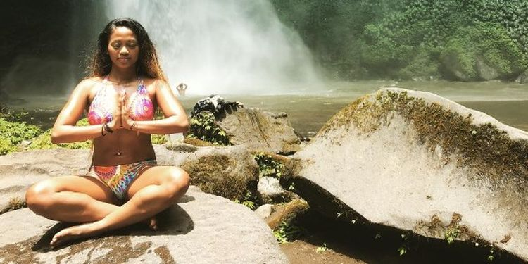 Image of the woman meditation near a waterfall