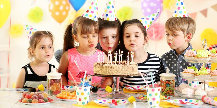 Photo of a happy group of children blowing candles on cake at birthday party