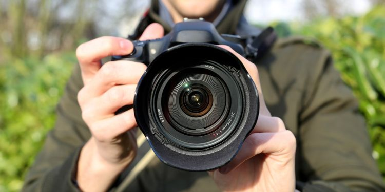 Photo of a man holding camera with large lens
