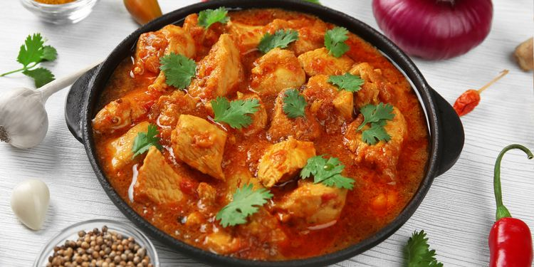 Photo of chicken curry with vegetables on wooden background