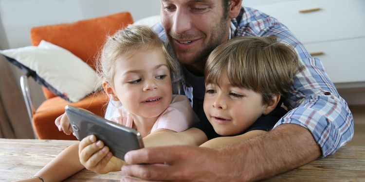 Photo of father and his kids playing with smartphone