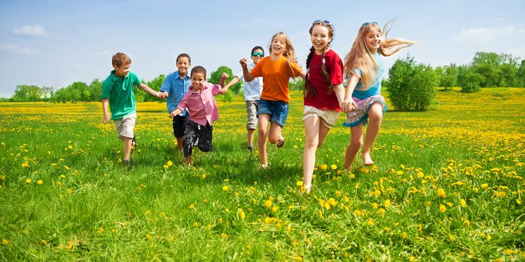 Photo of group of kids running in the dandelion spring field