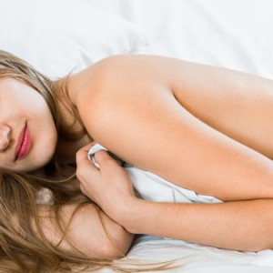 Photo of brunette young girl sleeping naked in bed at home