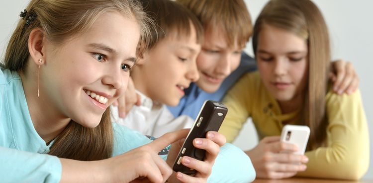 Photo of children smiling and playing on smarphones
