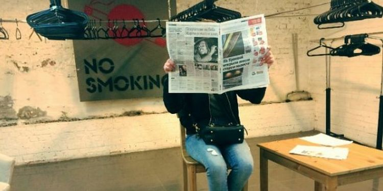 Image of a girl reading a newspaper