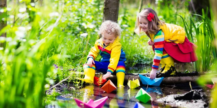Photo of children play with colorful paper boats in a small river on a sunny spring day