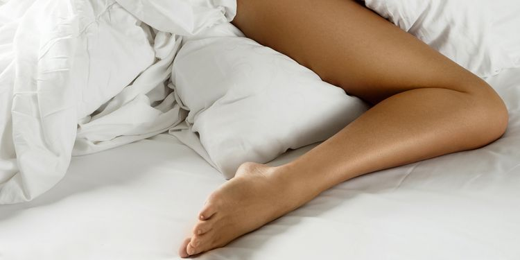 Photo of female naked leg on bed with uncovered sheets