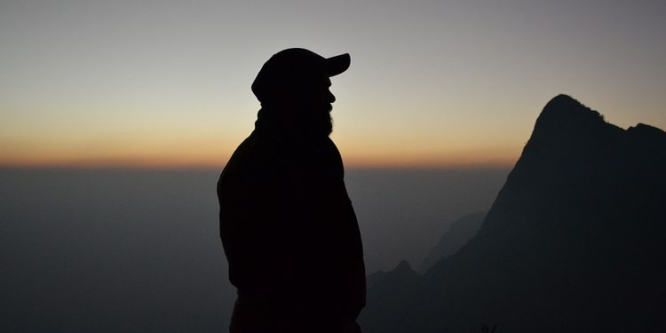 Photo of a human silhouette in sunset with mountains in background