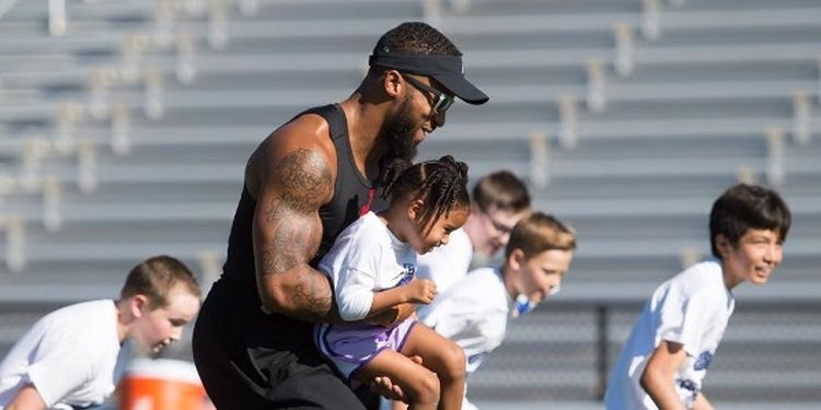 Image of Earl Thomas holding a girl