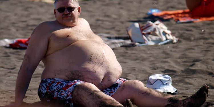 Image of the man suffering from obese on the beach