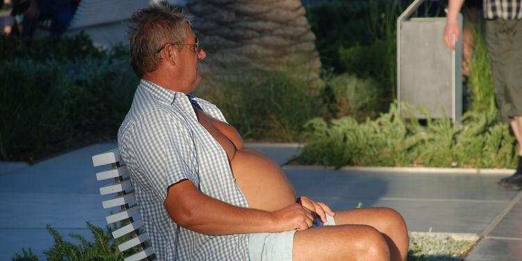 Photo of a bloated man sitting on a bench