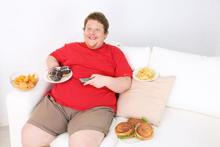 Photo of a Lazy overweight male sitting with fast food on couch and watching television