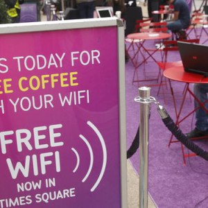 Photo of people sitting in open wifi cafe surfing internet