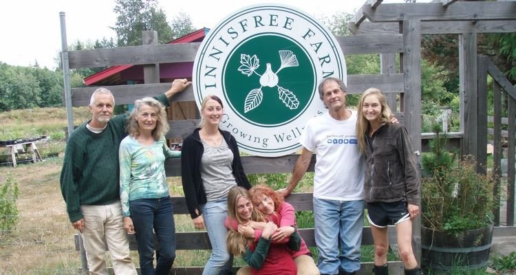 Photo of people from Innisfree farm with seal of farm